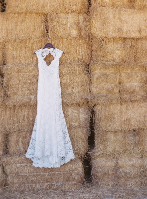 Monique Lhuillier wedding dress hanging on hay stack