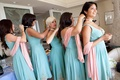 Bridesmaids in blue dresses putting on matching necklaces