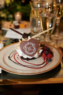 gourmet chocolate dessert with monogram, raspberries and blueberries