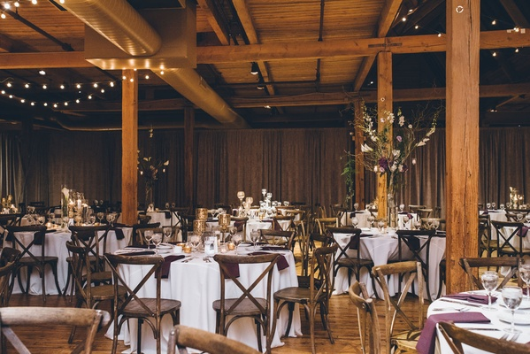 Rustic wedding reception round tables with wood chairs and wood beams ceilings, floors, purple