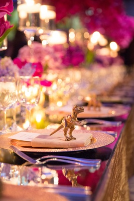 Wedding reception place setting topped with a golden dinosaur figurine