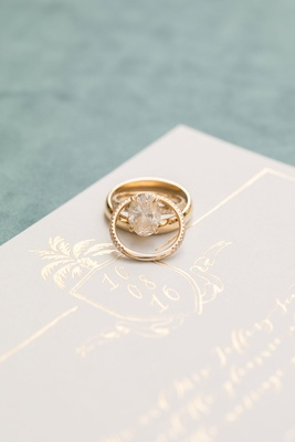 White invitation with gold foil crest oval cut diamond engagement ring wedding band on invite