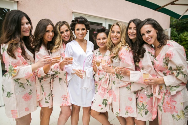 White silk robe for bride in hair rollers and ivory pink green flower print robes for bridesmaids