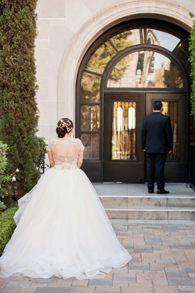 Back of bride in Lazaro wedding dress waiting for groom during First Look at wedding
