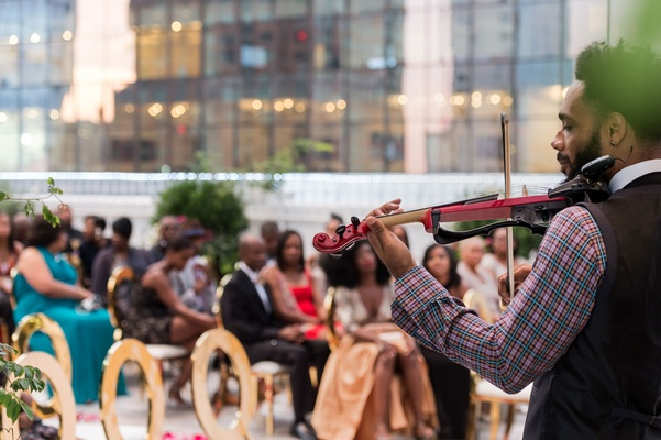 Musician at front of ceremony playing songs on electric violin wedding entertainment idea