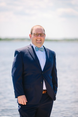 groom in glasses and navy suit with bright blue patterned bow tie