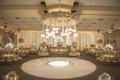 Wedding reception with white dance floor, gold monogram, flower chandelier with lanterns