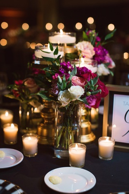 pink, black, and white wedding reception, dark pink flowers, votive candles, floating candles