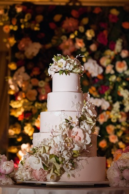 Five layer wedding cake with flowers and light pink fondant