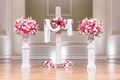 wedding ceremony church altar wood cross pink white flowers urns