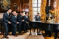 groom and groomsmen playfully act out a performance in their tuxedos with piano
