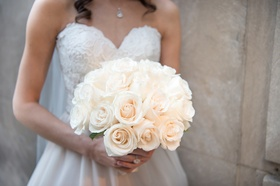 bride in essence of australia wedding dress holds bridal bouquet of ivory roses