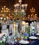 Wedding reception high gloss table gold flatware blue purple flower centerpiece candles taper