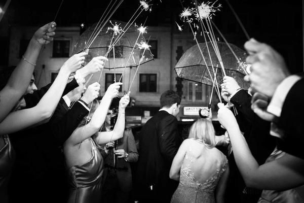 black and white photo of bride and groom getting into getaway car guests with sparklers umbrellas