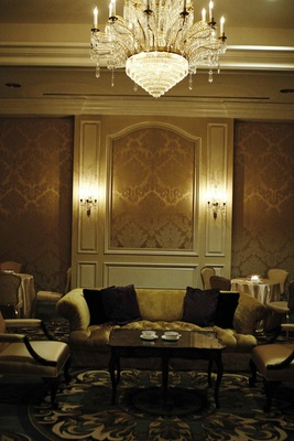 Wedding lounge area with a chandelier, golden wallpaper and furnishings