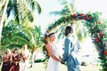bride in lihi hod, groom in grey suit, maui wedding, flower arch with purple and red flowers