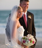 bride carrying bouquet stands with groom on beach