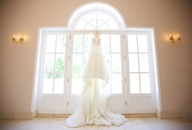 Bridal gown with cathedral length train hanging from top of window door at chateau wedding venue