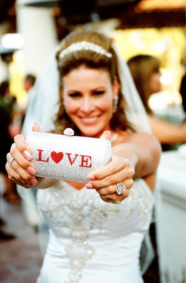 Bride holding crystal purse with red LOVE sign
