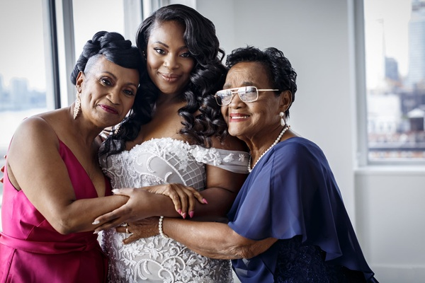 Bride in off shoulder wedding dress with mom and grandma before wedding ceremony