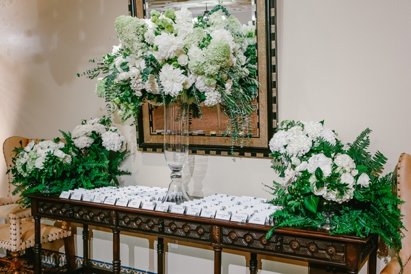 floral arrangements of white flowers, ferns, escort cards