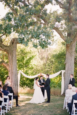 Bride and groom at outdoor ceremony between two oak trees decorated with cloth and a cross