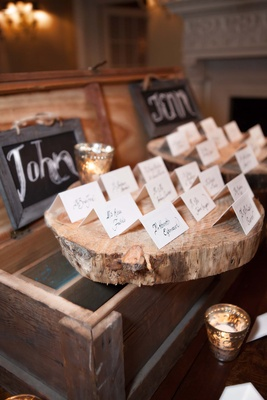 Wedding reception with place cards displayed on wood slabs on top of distressed wood crates