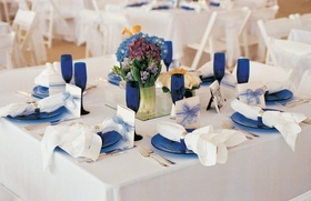 Square white table with blue plates, goblets, and centerpieces