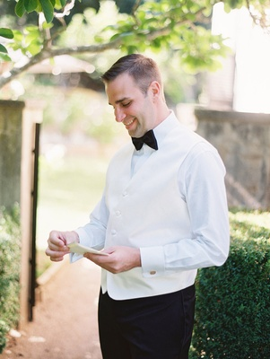 a groom in tuxedo with black bow tie smiling while he reads a card from bride outdoors