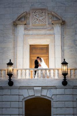 Wedding portrait bride and groom on romeo and juliet balcony lantern sconces doors marble