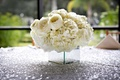 Ivory hydrangea and white garden rose flower arrangement on silver sequin wedding table
