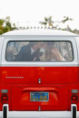 Bride and groom kiss in back window of 1971 Volkswagen red bus
