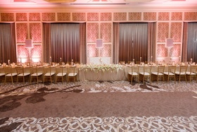 sweetheart table with tufted white seating in between two long king's tables, gold chiavari chairs