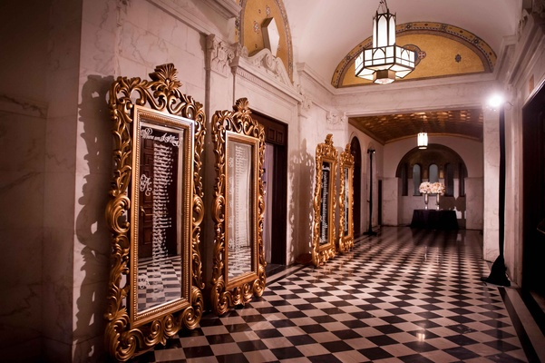 Ornate gold mirror frames in black and white checkered floor hallway at Vibiana with seating chart
