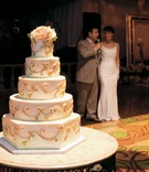 Wedding cake with golden swirls and light green beading