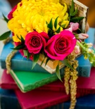 yellow mum, small magenta roses, stack of colorful books