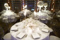 white tables and centerpieces, ghost chairs, crystal chargers white ivory flowers
