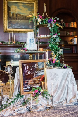 dessert station with framed mirror sign blue wedding cake greenery