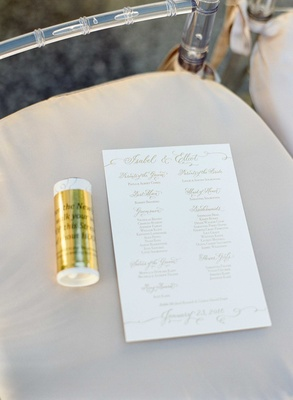 Lucite chair with beige cushion white and gold ceremony program with list of wedding party parents