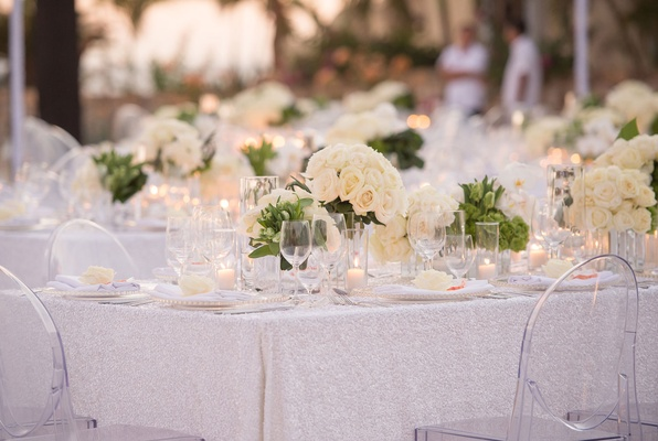ghost chairs, glittery silver linens, mirror box with ivory flowers and greenery