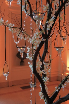 Branch centerpiece with crystals, orchids, and candles