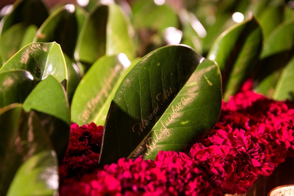 Wedding details ideas real greenery leaf with gold calligraphy on bed of red flowers