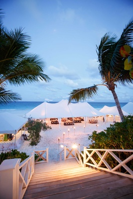 Stairway to beach tent wedding tiki torch candle lights on sand leading to reception in the Bahamas