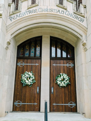 wedding ceremony peachtree christian church atlanta wood doors green white wreaths decor winter