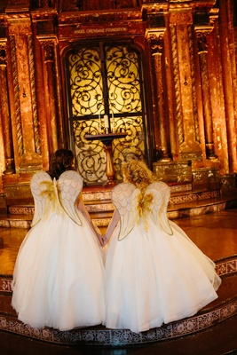 Two flower girls with angel wings on back