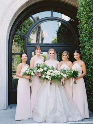 bride in sparkling lazaro wedding dress bridesmaids in hayley paige light pink halter neck dresses