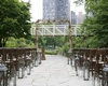 Summer in the city. A rustic birch chuppah overlooks a lush green park in Chicago.