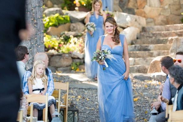 bridesmaids dressed in blue walk down stone and gravel aisle