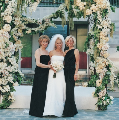 bride and mother under floral chuppah