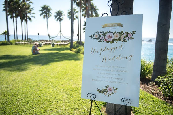 Oceanfront wedding ceremony with Unplugged Wedding sign decorated with printed yellow, pink roses